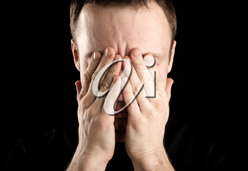 Portrait of young stressed Caucasian man covers his face with hands isolated on black background