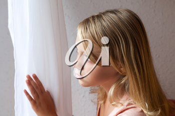 Beautiful blond Caucasian girl looking in a window with white curtains, closeup portrait