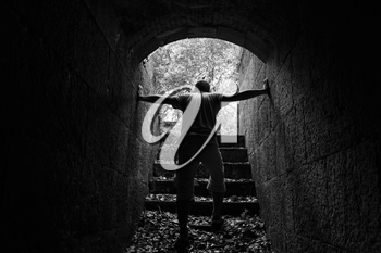 Tired man goes out of dark stone tunnel with glowing end, monochrome photo