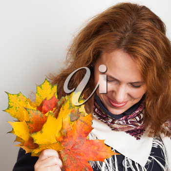 Portrait of beautiful smiling Young woman with colorful autumn maple leaves, square photo