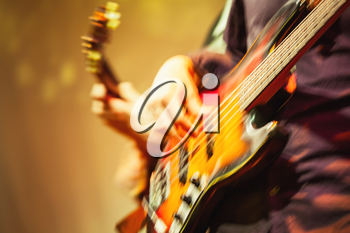 Colorful blurred rock music background, guitar players on a stage, motion blur effect and  retro tonal correction filter, old instagram style