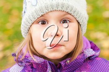 Funny smiling Caucasian little girl, close up outdoor portrait, walking in autumnal park