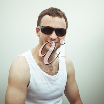 Portrait of Young sporty smiling European man in white shirt and black sunglasses, vintage toned square photo