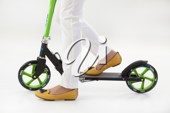Woman's legs on a push-cycle on isolated background