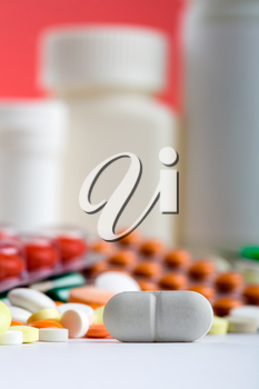 Closeup of white pill with various medicines on background