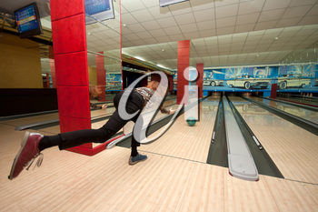 Funny beginner girl playing bowling. Wide angle