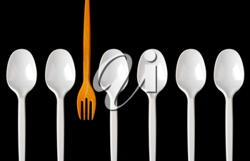 A row of plastic spoons and one yellow fork. Isolated on white