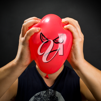 Man squeezing red balloon with angry smiley
