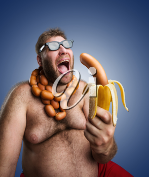 Mad man in glasses with sausages round his neck holds a big wurst in bananas peel over blue