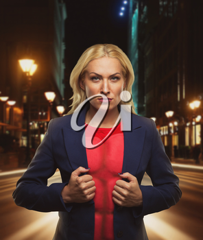 Strong woman superhero showing off her strength in night city street