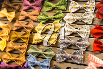 Multicolored vintage bow-ties with flowers on the board