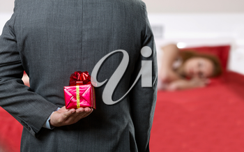 Businessman hiding a gift for his wife behind his back