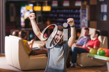 Young bearded man celebrating his victory in bowling
