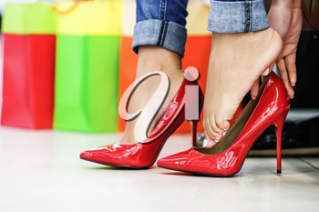 Close up of woman fitting red elegant stilettos