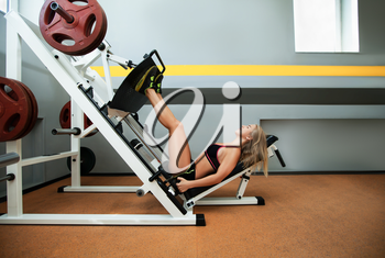 Side view of young girl training legs on the sport machine