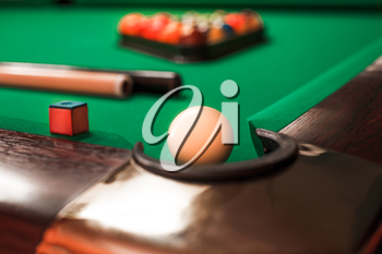 White billiard ball opposite to a pocket. Cue and triangle with balls on the background.