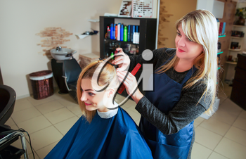 Hairdresser prepares for work with young woman in hairdressing salon.