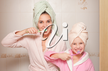 Happy mother and little daughter with toothbrushes teaching to brush their teeth in bathroom.