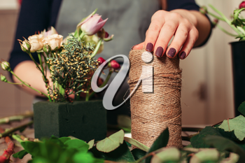 Florist at work: Woman creating modern bouquet of different flowers.