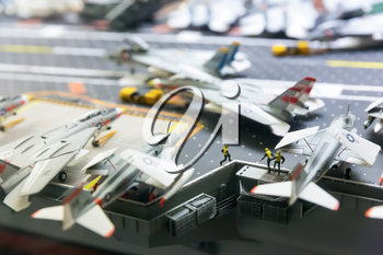 Miniature model of aircraft carrier runway with planes and people figures.