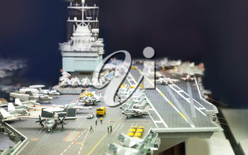 Miniature model of aircraft carrier on black background.