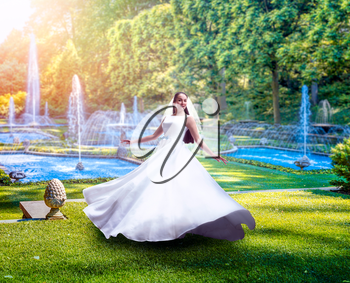 Young bride in white dress, green park with fountains on background