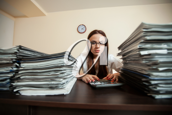 Doomed female accountant against big stacks of documents and calculator