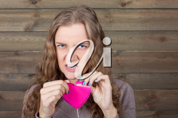 Young girl with angry face holding pink heart on a stick in her hands, wooden background. Fun photo props and accessories for shoots
