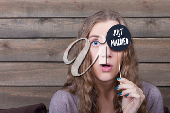 Young smiling woman holding funny icon on a stick with just married inscription, wooden background. Fun photo props and accessories for shoots