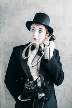 Pantomime theater actor with makeup mask performing with retro telephone. Comedy artist in suit, gloves and hat
