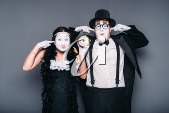 Pantomime actors performing with alarm clock. Comedy artist and actress waiting for bomb explosion. Mime theater performers