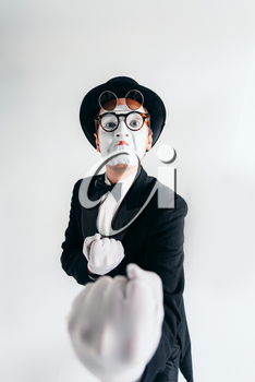 Comedy mime artist in glasses and white makeup mask. Pantomime in suit, gloves and hat. April fools day concept
