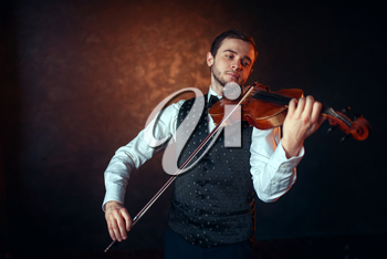 Portrait of male fiddler playing classical music on violin. Violinist man with musical instrument