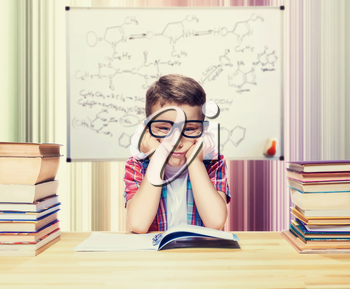Little boy learns homework in the school library. Pupil in glasses against book shelves