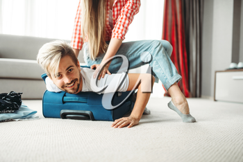 Cheerful girl Packed her husband in a suitcase. Fees on vacation concept