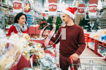 Happy couple buying christmas souvenirs in supermarket, family tradition. December shopping of new year goods