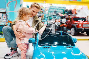 Mother with her little girl choosing electromobile in kids store. Mom and child buying toys in supermarket together, family shopping