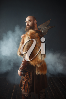 Portrait of viking with axe, martial spirit, barbarian image. Ancient warrior in smoke on dark background