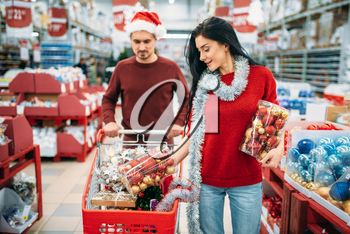 Young couple buying a lot of Christmas decorations in supermarket, family tradition. December shopping of holiday goods