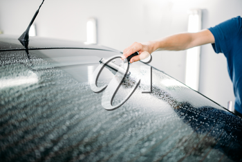Male specialist work with window, car tinting film installation process, installing procedure,