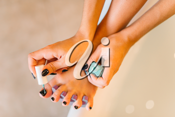 Female person hands with nail polish, pedicure procedure closeup. Nailcare treatment process