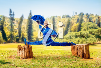 Female wushu master with fan sits on a twine, martial arts, green forest on background. Woman in blue cloth on outdoor fight training