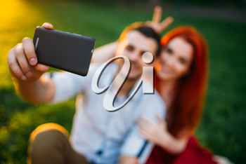 Love couple makes selfie on phone camera in summer park on sunset. Romantic date of attractive woman and young man