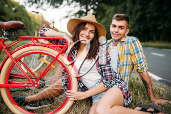 Love couple with vintage bikes sitting on roadside. Romantic journey of young man and woman. Boyfriend and girlfriend together outdoor, retro bicycle