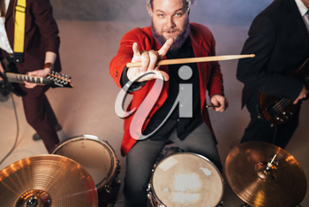 Drummer in red suit, performing on the stage of night club, electro and bas-guitarists on background. Rock band concert, music show