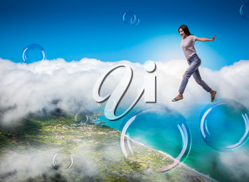 Cute woman jumping in the sky on big soap bubbles. Female person blowing colorful balloons