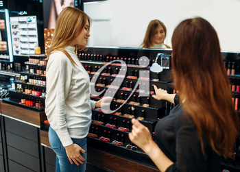 Seller consultant and female customer in the make-up shop. Cosmetic choosing in beauty store