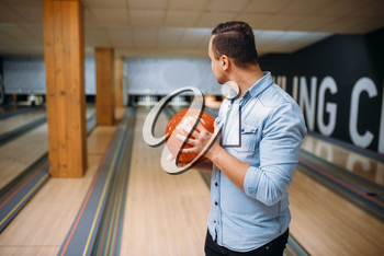 Male bowler standing on lane and poses with ball in hands, back view. Bowling alley player prepares to throw strike shot in club, active leisure
