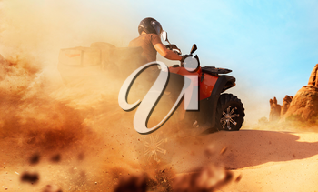 Atv riding in sand quarry, dust clouds. Male driver in helmet on quad bike, extreme freeriding on quadbike in desert dunes