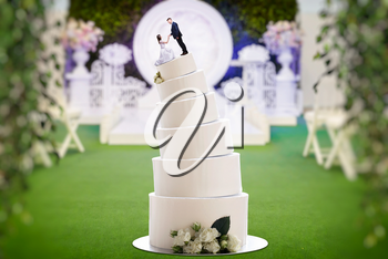 Wedding cake with bride and groom figures on the top, marriage proposal. Sweet pie for newlyweds with little figurines
